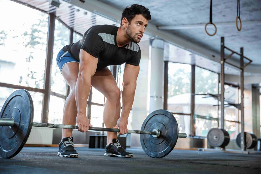 Man doing deadlifts to improve strength on quads, knees and glutes